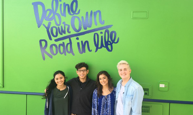 4 students in front of bright green tour bus that says define your own road in life