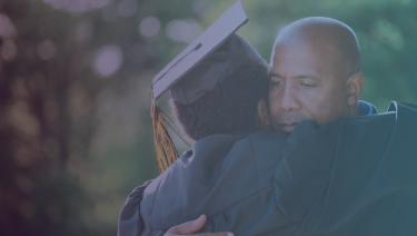 Father and son hugging, son wearing graduation cap