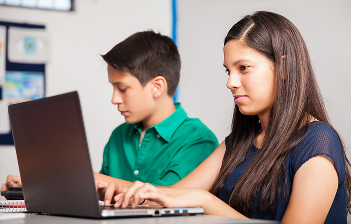 Two middle school aged children at laptops