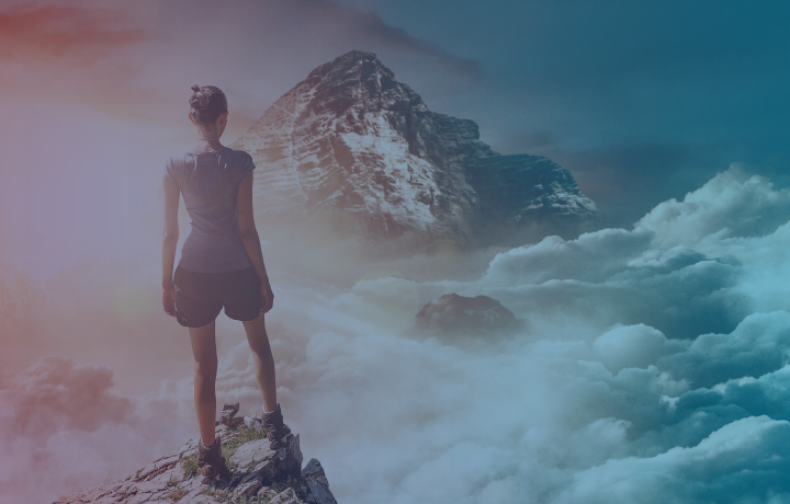 Girl standing on mountain top looking out across clouds